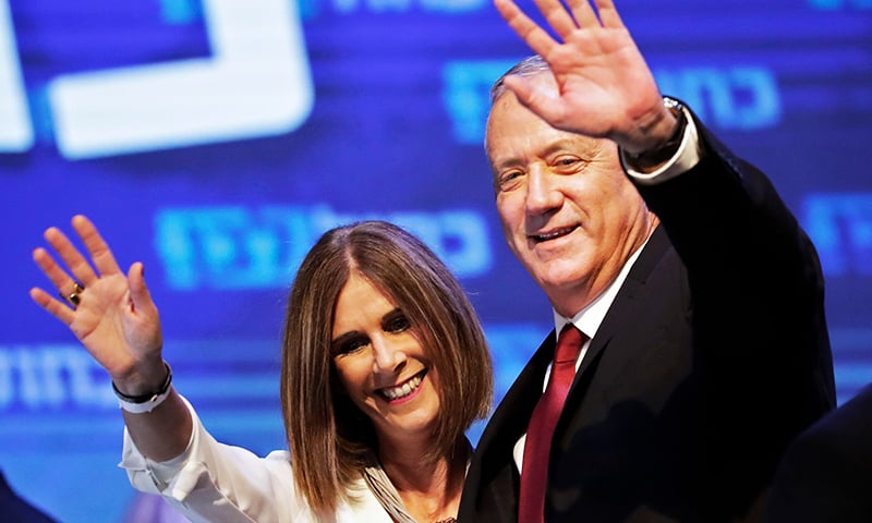Benny Gantz (R), leader and candidate of the Israel Resilience party that is part of the Blue and White (Kahol Lavan) political alliance, waves to supporters alongside his wife Revital Gantz. — AFP
