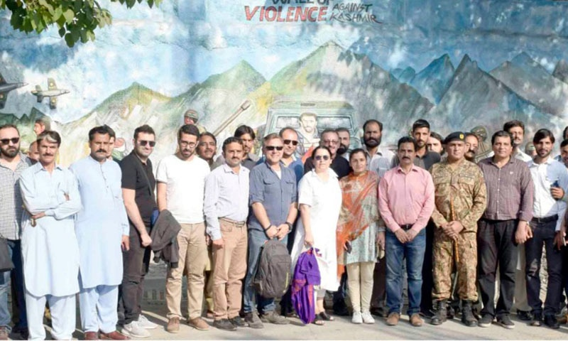 Visiting Turkish delegation poses for a photograph with Muzaffarabad based journalists in front of a wall near press club that depicts Indian atrocities in occupied Kashmir through embossed images. — Photo by author