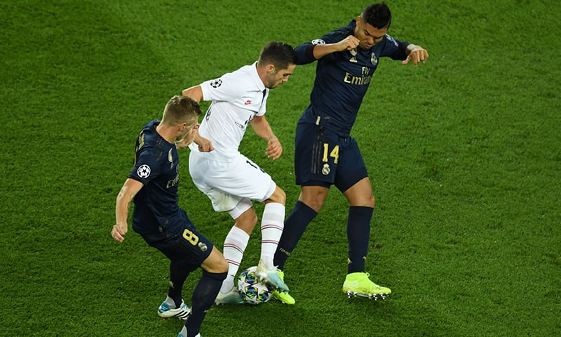 Paris Saint-Germain's Spanish midfielder Pablo Sarabia (C) fights for the ball with Real Madrid's German midfielder Toni Kroos (L) and Real Madrid's Brazilian midfielder Casemiro (R) during the UEFA Champions league Group A football match between Paris Saint-Germain and Real Madrid, at the Parc des Princes stadium, in Paris, on September 18, 2019. — AFP