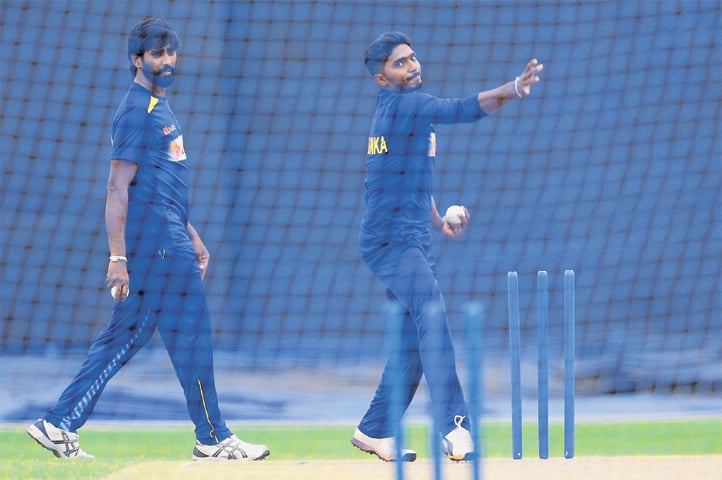 COLOMBO: Sri Lankan spinner Lakshan Sandakan bowls as team-mate Nuwan Pradeep looks on during a practice session at the R. Premadasa Stadium on Thursday.—AFP