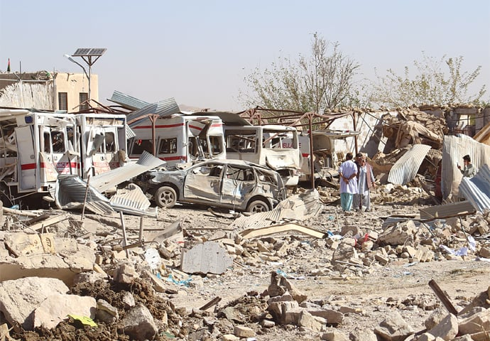 QALAT: Destroyed and damaged vehicles are seen at the site of a bomb attack in the capital of Zabul province on Thursday.—Reuters