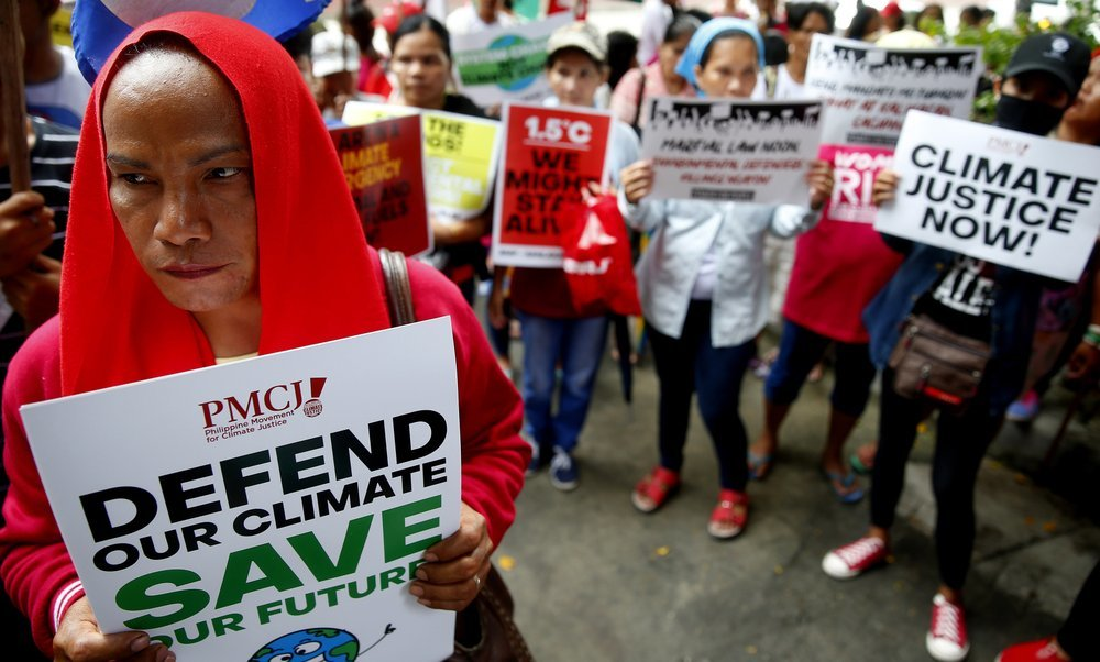 Environmental activists hold placards during a rally outside the Department of Environment and Natural Resources on Friday at suburban Quezon city, Philippines. ─ AP