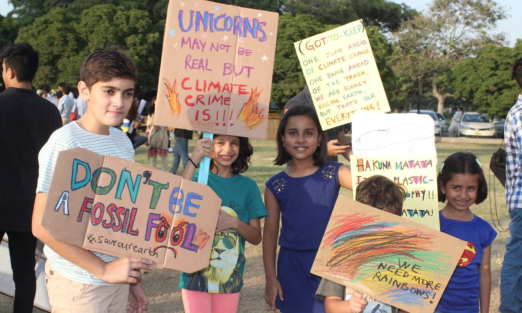 Children hold up placards at the climate march. — Photo by Kamran Nafees