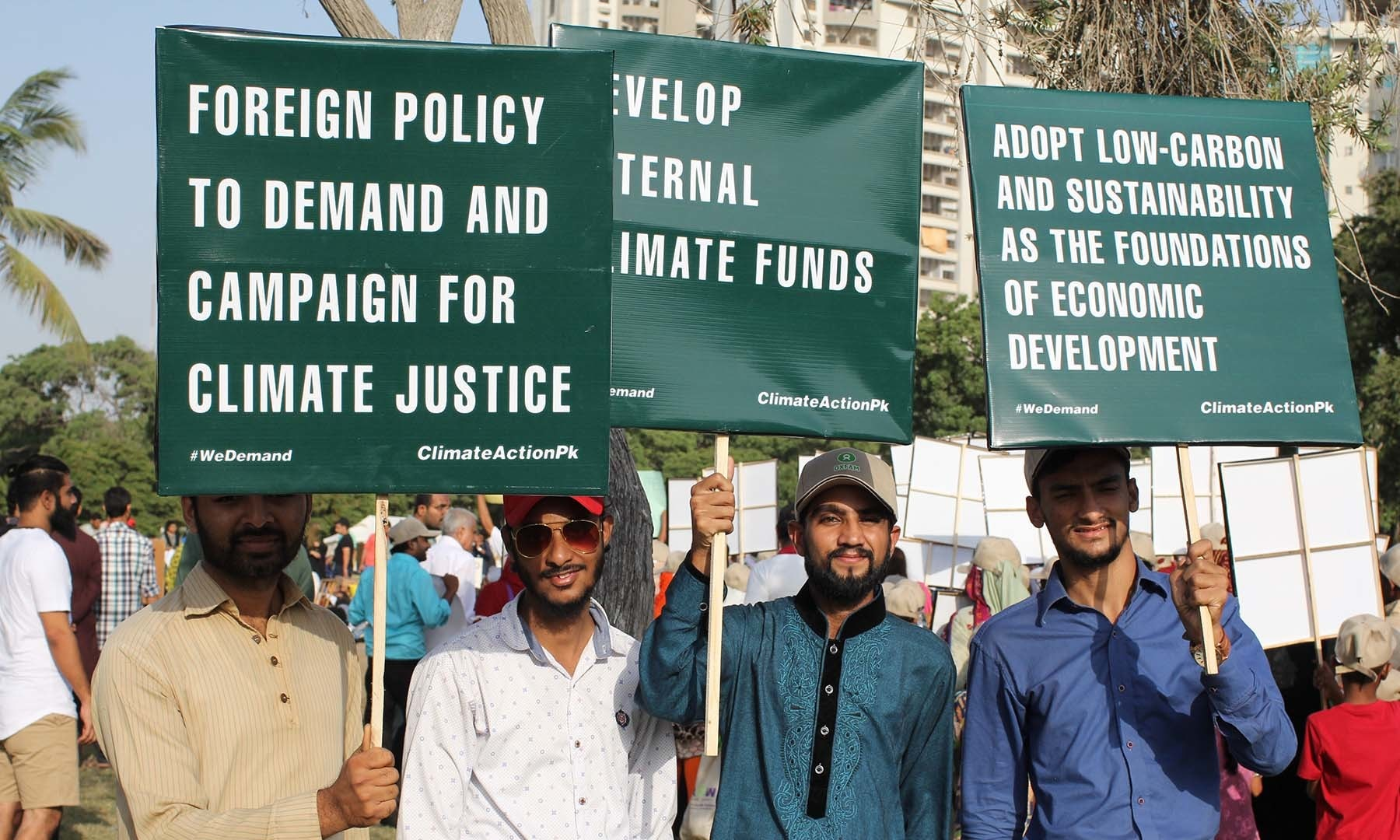 Attendees hold up posters at the climate march in Karachi. — Photo by Kamran Nafees
