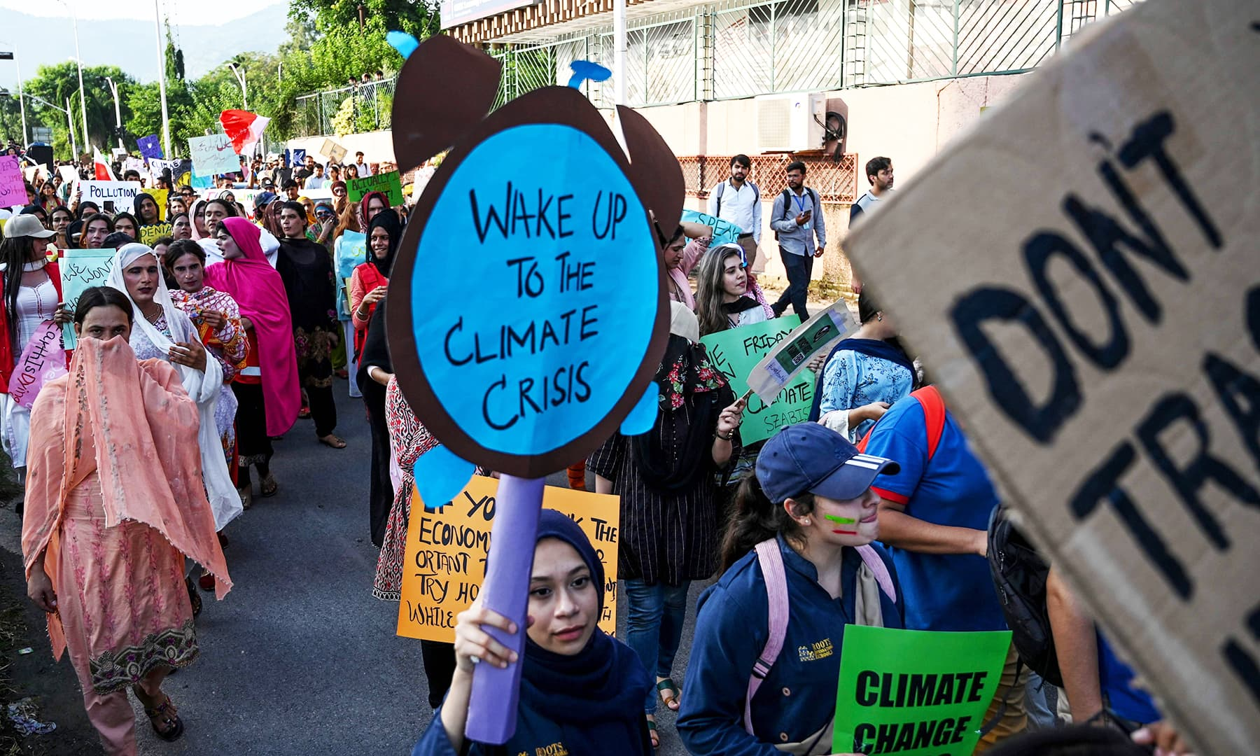 Youths hold placards in Islamabad as they march for a climate strike to protest against governmental inaction towards climate breakdown and environmental pollution.— AFP