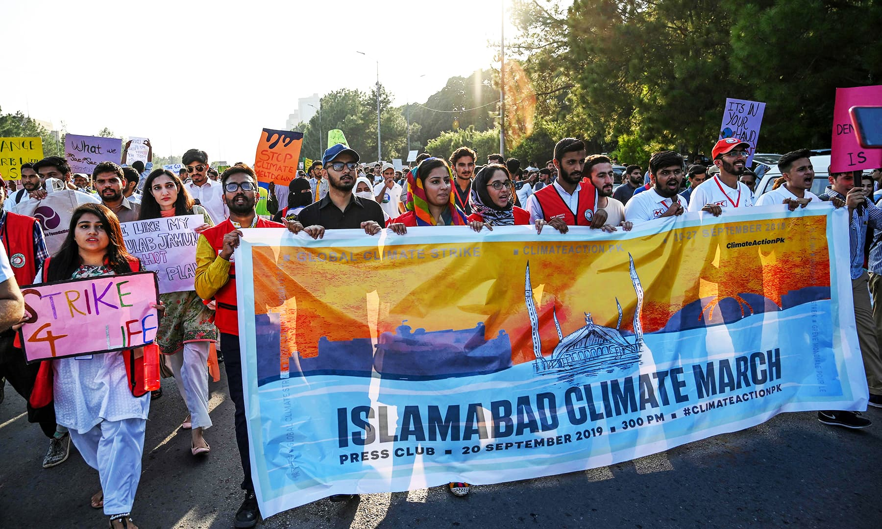 Youths hold placards in Islamabad as they march for a climate strike to protest against governmental inaction towards climate breakdown. — AFP