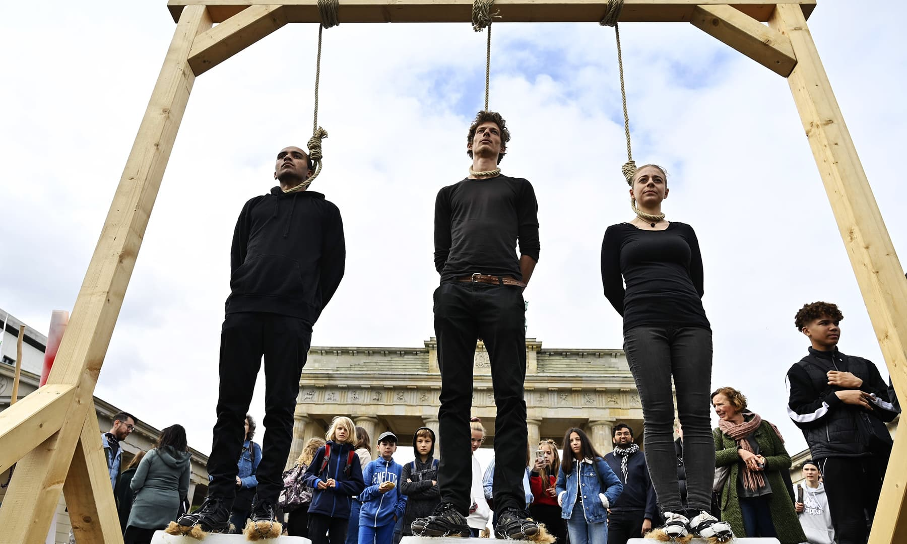 "Protesters stand on blocks of ice while standing under gallows during the ""Fridays for Future"" demonstration at the Brandenburg Gate in Berlin as a protest for climate action. — AFP"