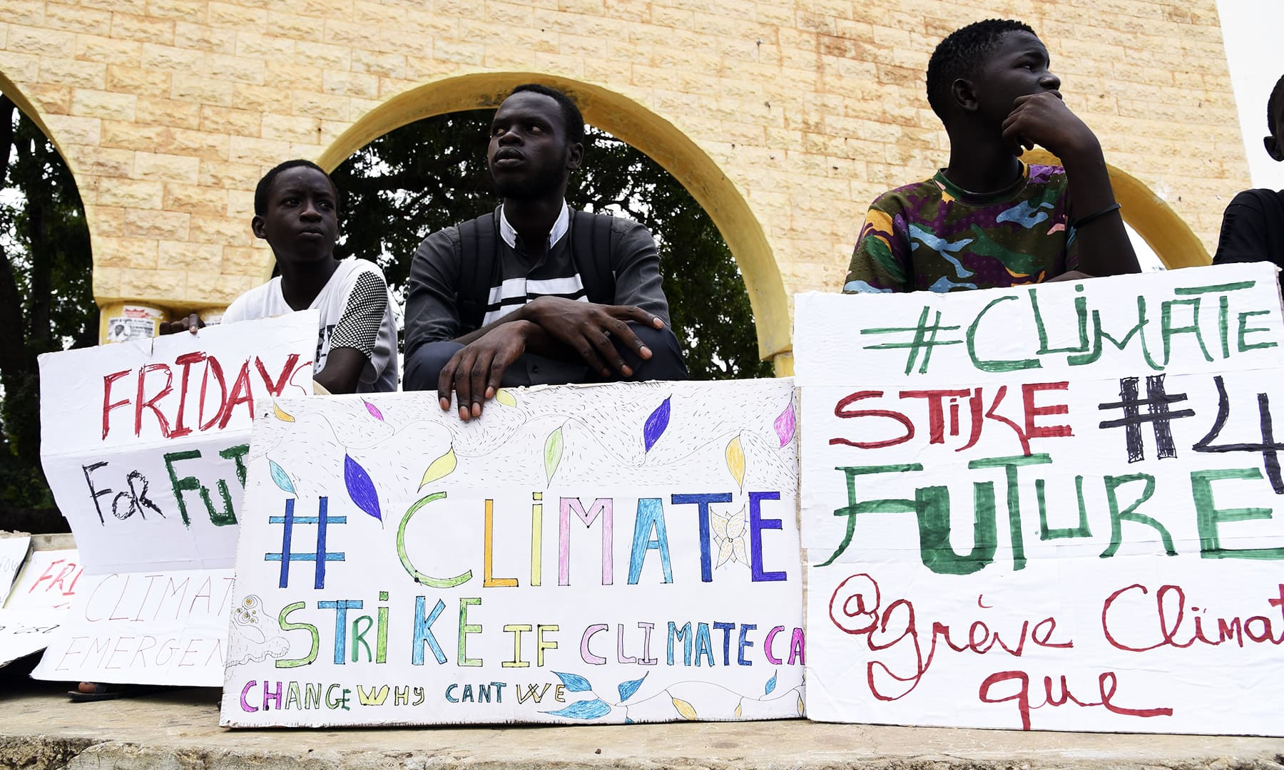 Demonstrators sits with banners during the Global Climate strike march on September 20, 2019 in Thies, Senegal. — AFP