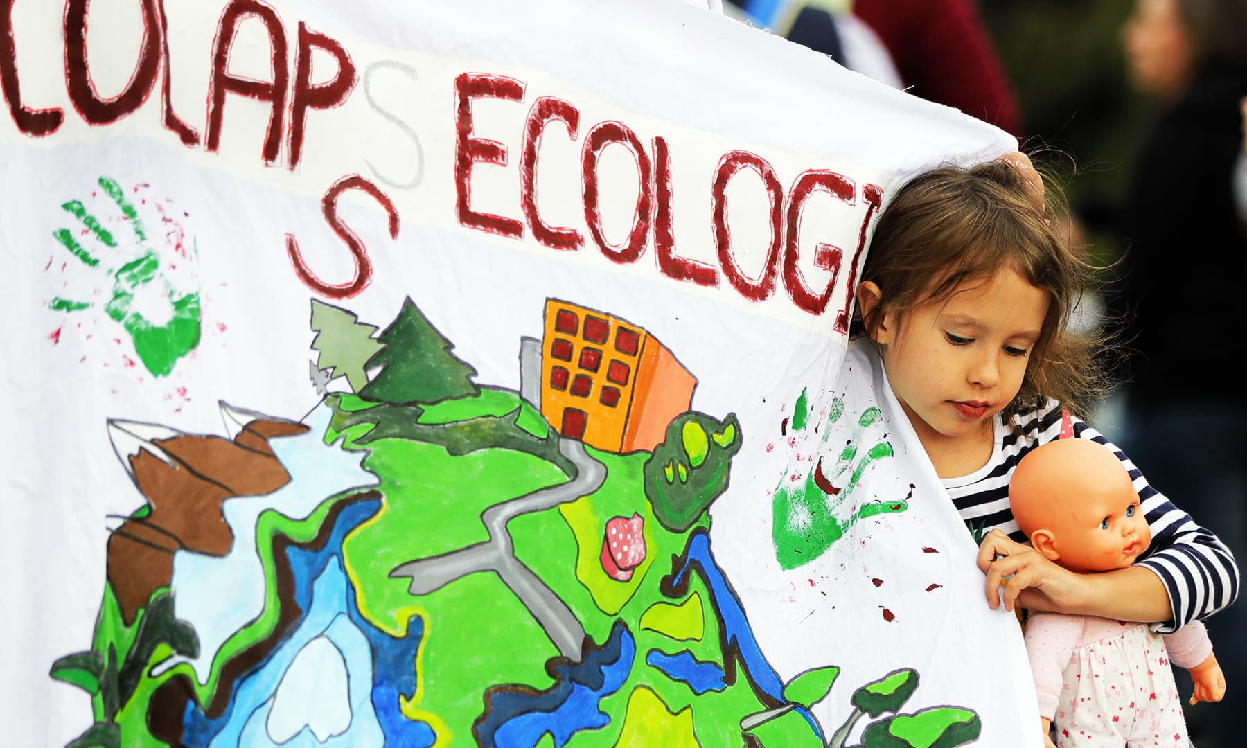 "A little girl hods a doll next to a banner that reads ""Ecological Meltdown"" during a Climate Change protest in Bucharest, Romania. — AP."