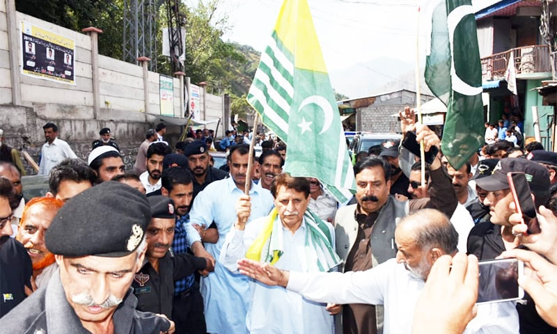 Holding an AJK flag, Prime Minister Raja Farooq Haider walks through Chinari Bazaar on his way to Chakothi.— Photo provided by author