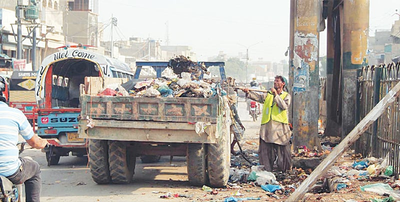 A sanitation worker loads trash onto a truck in the Pak Colony area as part of the campaign on Saturday.—Online