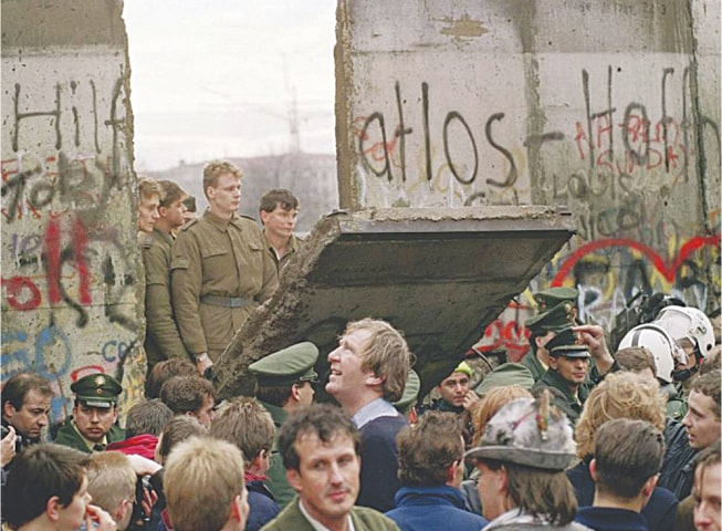 Police from both sides stands idly by as the Berlin Wall is breached at the Sandkrug Bridge crossing-point on Invaliden Strasse, in November 1989
