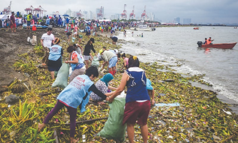 MANILA: Volunteers collect trash as they participate in World Cleanup Day on Saturday. — AFP