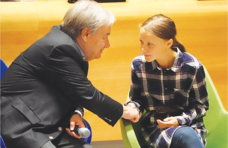 NEW YORK: UN Secretary-General Antonio Guterres shakes hands with environmental activist Greta Thunberg at the Youth Climate Summit on Saturday.—Reuters