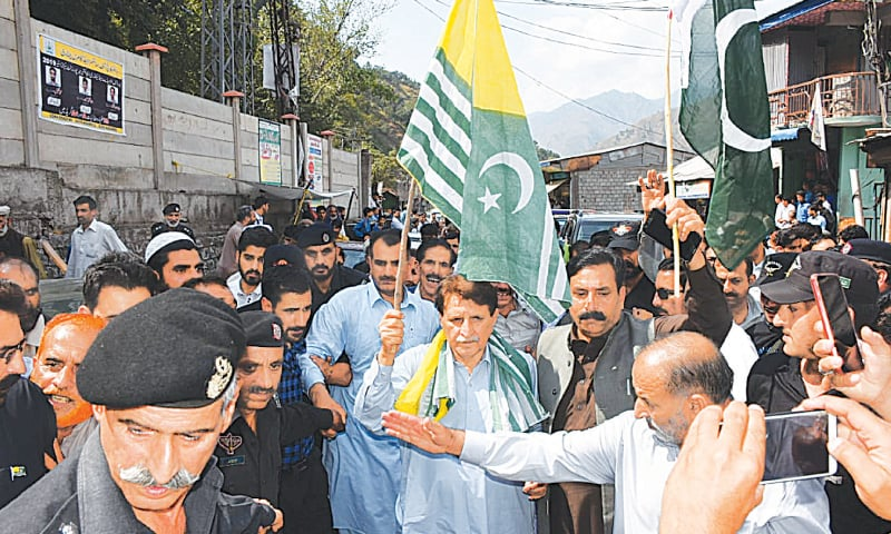 HOLDING an AJK flag, Prime Minister Raja Farooq Haider on Saturday walks through Chinari Bazaar on his way to Chakothi, where he addressed victims of Indian shelling.—Dawn