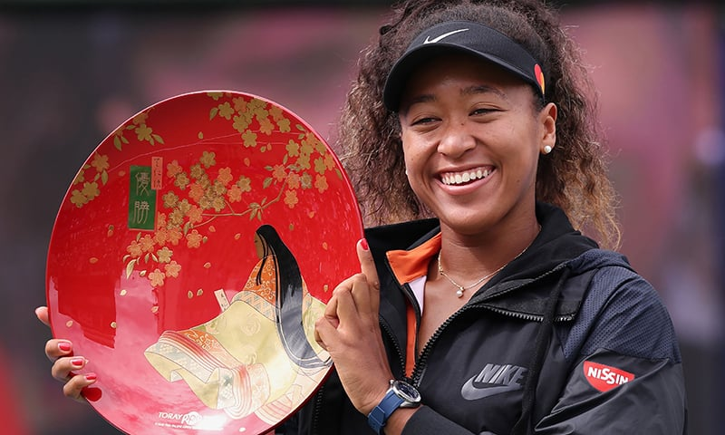 Pan Pacific Open women's singles winner Naomi Osaka holds a victory plate during the awarding ceremony in Osaka on September 22, 2019. — AFP
