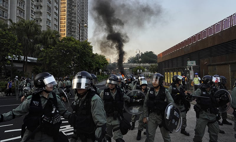 Riot police march past a burning barricade during a protest in Hong Kong on Sunday, September 22, 2019. — AP
