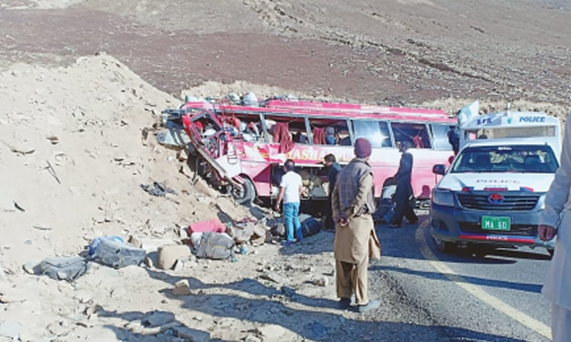 (Top) A man looks at the wreckage of the bus after the accident in Gattidas area on Sunday and (bottom) injured persons being treated on a Pakistan Army helicopter.—Dawn/APP