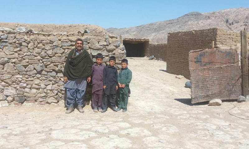 GHULAM Mohammad Mohammadzai and his children pictured in front of their home. — Dawn