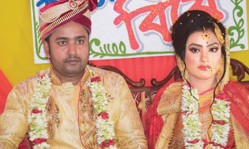 Groom Tariqul Islam and bride Khadiza  Akter Khushi pose for a photo during their wedding.—AFP