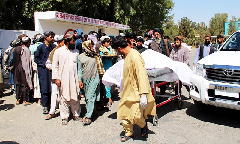 Afghan villagers carry a dead body on a stretcher outside a hospital following an airstrike in Lashkar Gah, the capital of Helmand province on September 23, 2019. — AFP