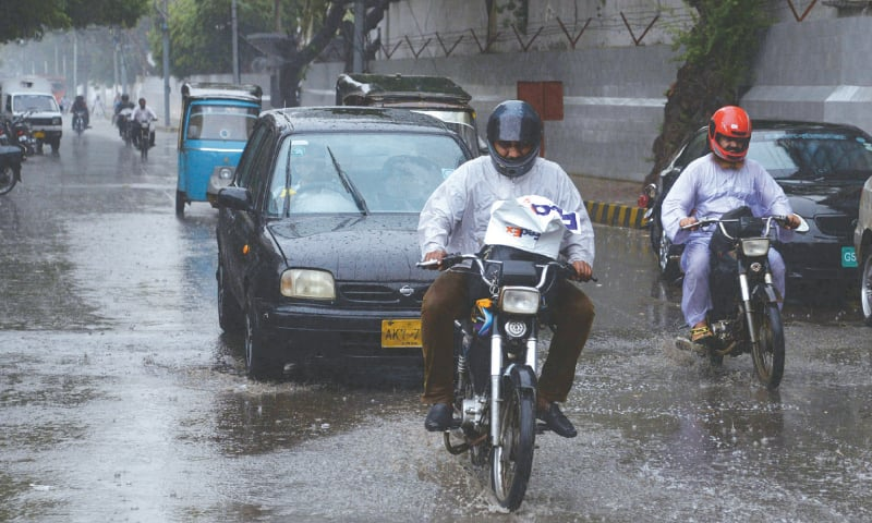 Motorists caught in the downpour in Saddar and (right) a massive snarl-up is seen on Korangi Road after the rainfall on Monday.—Shakil Adil / White Star