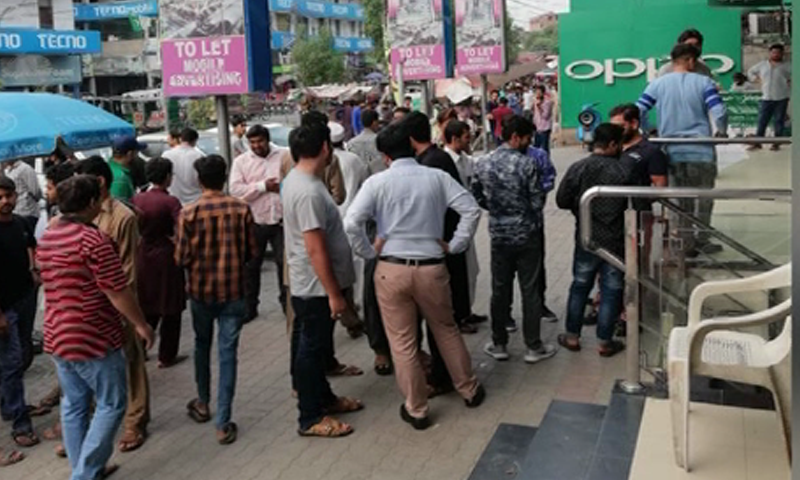 People stand outside a building in Lahore after the earthquake. — DawnNewsTV
