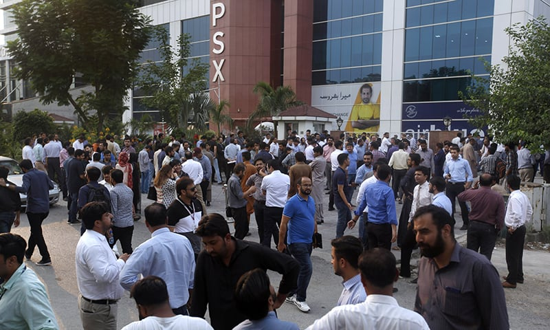 People stand outside their office after the earthquake was felt in Islamabad on Tuesday. — AP