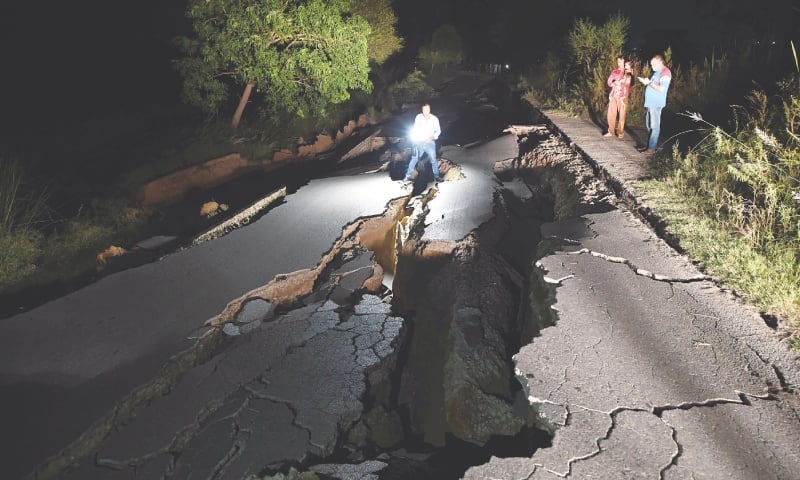 MIRPUR (Azad Kashmir): A news cameraman films a damaged road after the earthquake on Tuesday. (Right) An aerial view of a collapsed bridge in Jatlan area.—AFP/INP