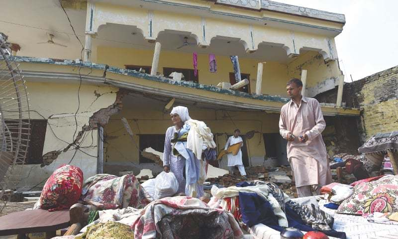 MIRPUR (AJK): Family members bring out their belongings from their damaged house in Saangmora Village on Wednesday.—Tanveer Shahzad / White Star