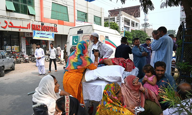Relatives stand in a street along with patients evacuated from a hospital following a quake of 4.7-magnitude in Mirpur on Thursday. — AFP