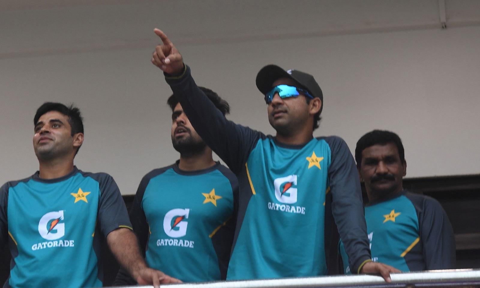 کراچی میں بارش کے دوران قومی ٹیم کے کپتان سرفراز احمد اور دیگر کھلاڑی موسم سے لطف اندوز ہورہے ہیں— فوٹو: اے ایف پی