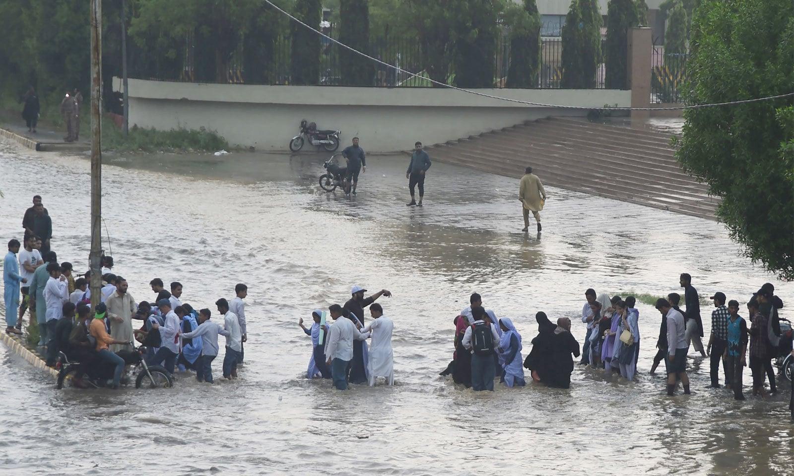 میچ دیکھنے کے لیے آنے والے شائقین اور اسکول کے بچے کراچی میں شدید بارش کے بعد جمع ہونے والے سے گزر کر اسٹیڈیم پہنچنے کی کوشش کر رہے ہیں— فوٹو: اے ایف پی