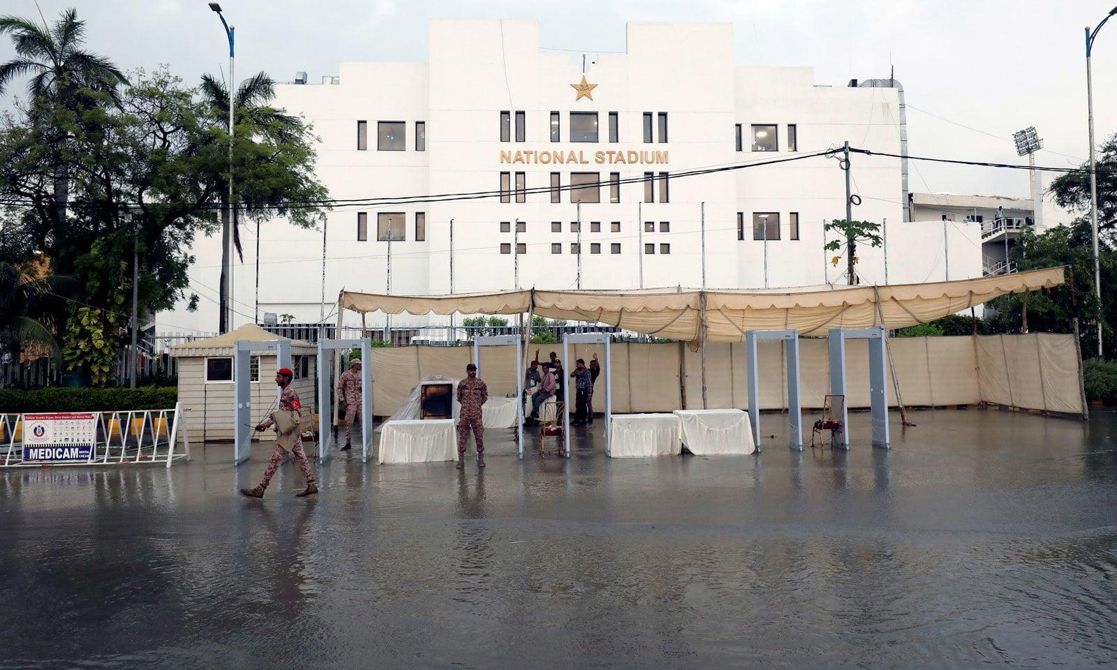 نیشنل اسٹیڈیم کے باہر شائقین کے لیے نصب واک تھر گیٹ کے پاس بھی بارش کا پانی جمع ہو گیا تھا— فوٹو: اے ایف پی