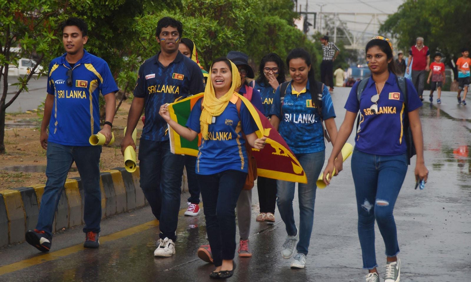 سری لنکن شائقین پہلے ون ڈے میچ میں اپنی ٹیم کو سپورٹ کرنے کے لیے اسٹیڈیم کی جانب رواں دواں ہیں— فوٹو: اے ایف پی