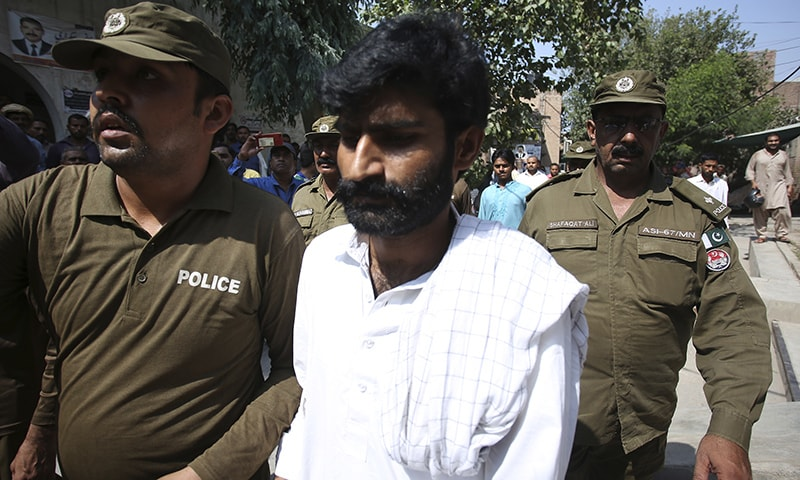 Police officers escort Mohammad Waseem, brother of Qandeel Baloch, at a court in Multan on Friday. — AP