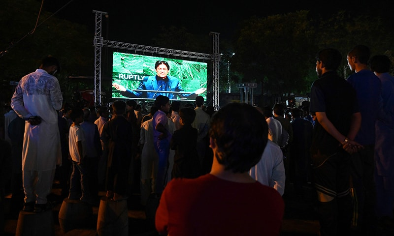 People watch Prime Minister Imran Khan addressing the United Nations General Assembly on a screen in Islamabad on Friday. — AFP