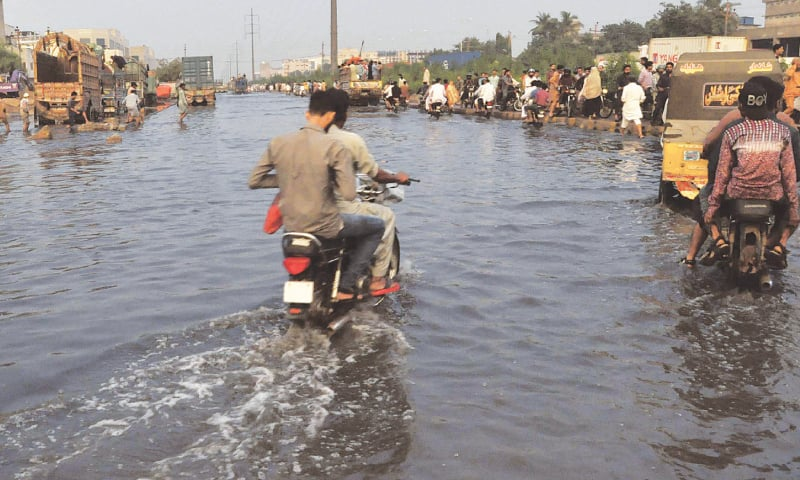 Motorists try to navigate through stagnant rainwater near Governor House in this PPI photo while (right) a similar situation persists in the Korangi Industrial Area on Friday, in this photograph by Shakil Adil.