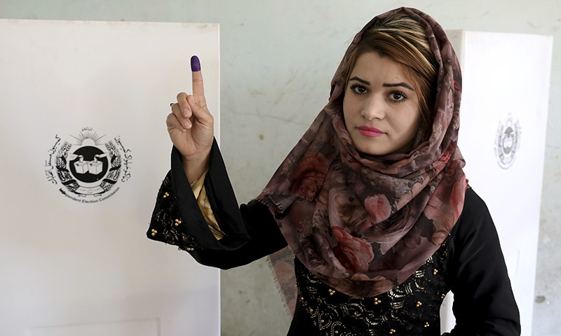 An Afghan woman shows her inked finger after casting her vote at a polling station in Kabul, Afghanistan, Saturday. — AP