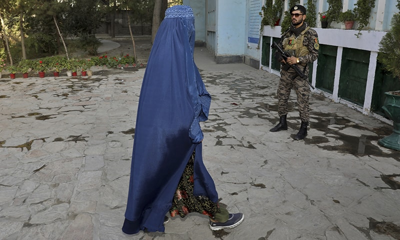An Afghan woman walks at a polling station during the presidential elections in Kabul on Saturday. — AP