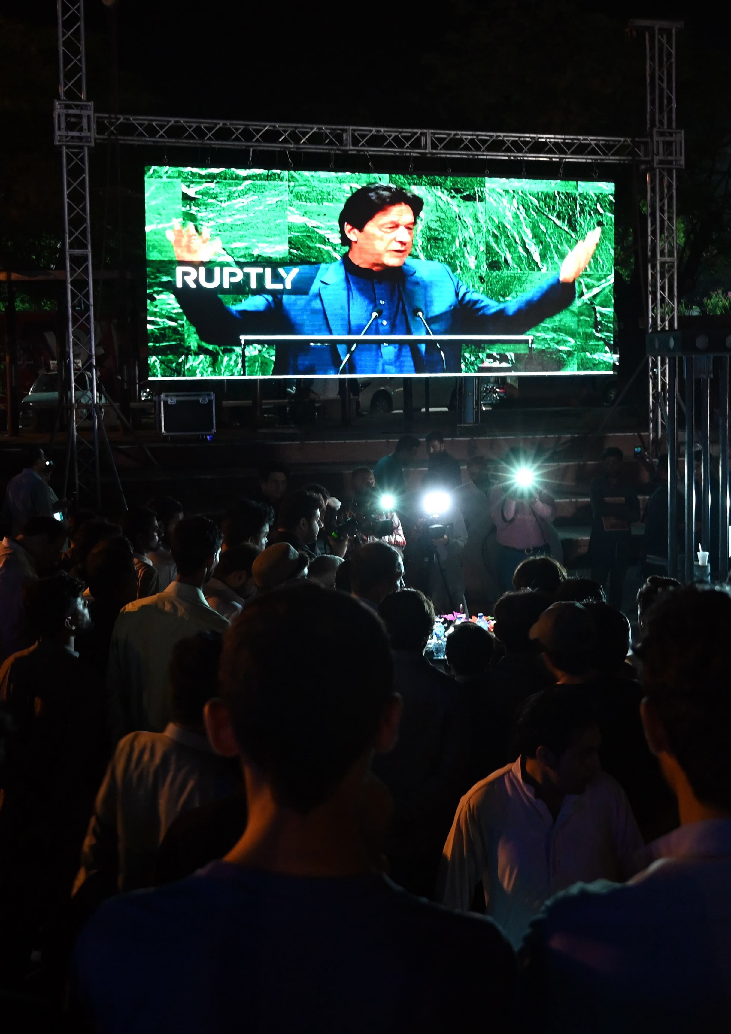 People watch PM Imran Khan addressing the UNGA on a screen in Islamabad. — AFP