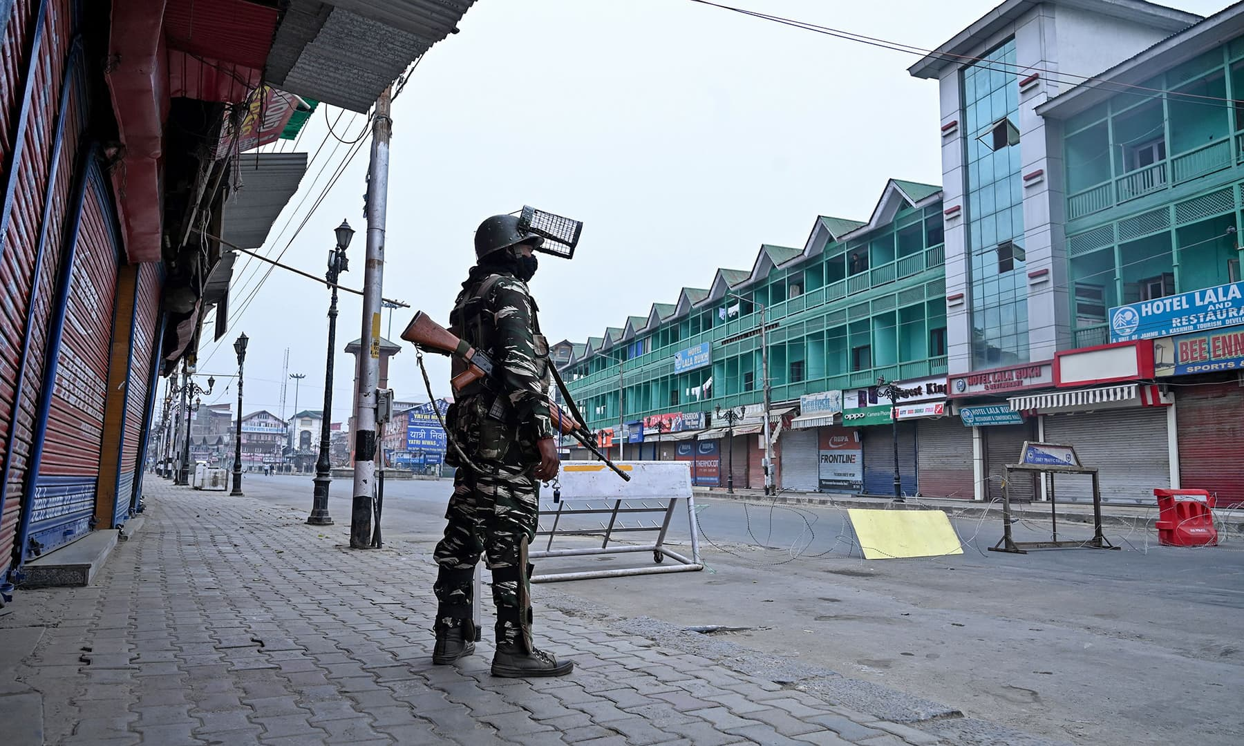 A security personnel stands guard to block a road near closed shops while strict restrictions are imposed during a lockdown in Srinagar on Saturday. — AFP