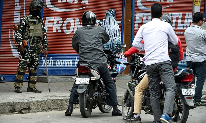 Security personnel stop commuters on motorcycles as they stand guard to block a road while strict restrictions are imposed during a lockdown in Srinagar on Saturday. — AFP
