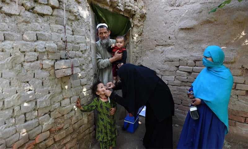 A polio worker administers polio drops to a young girl in Khyber Pakhtunkhwa | White Star