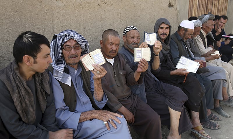 Men line up outside a polling station and shows their national ID card in western neighborhood of Kabul, Afghanistan, Saturday, Sept. 28, 2019. Afghans headed to the polls on Saturday to elect a new president amid high security and threats of violence from Taliban militants, who warned citizens to stay away from polling stations or risk being hurt. (AP Photo/Rahmat Gul) — Copyright 2019 The Associated Press. All rights reserved.