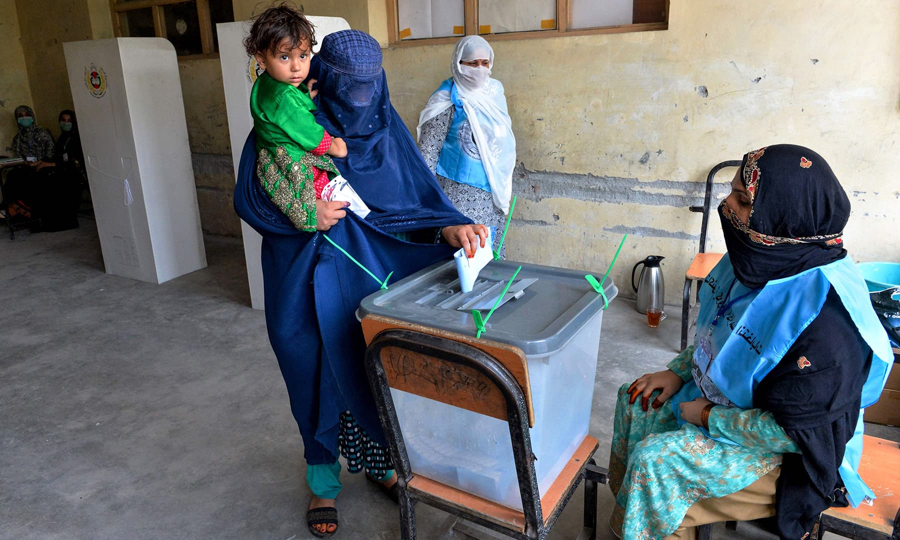 A woman holds her child as she casts her vote at a polling station in Jalalabad. — AFP