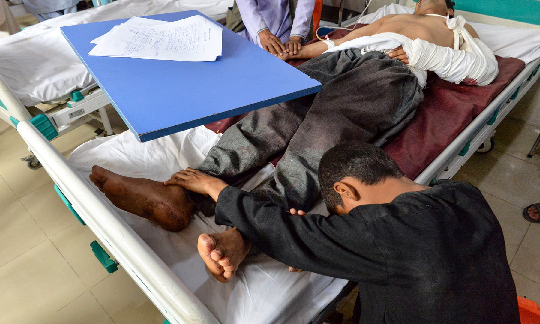 A wounded man receives treatment at a hospital after a blast as his son touches his feet in Jalalabad. — AFP