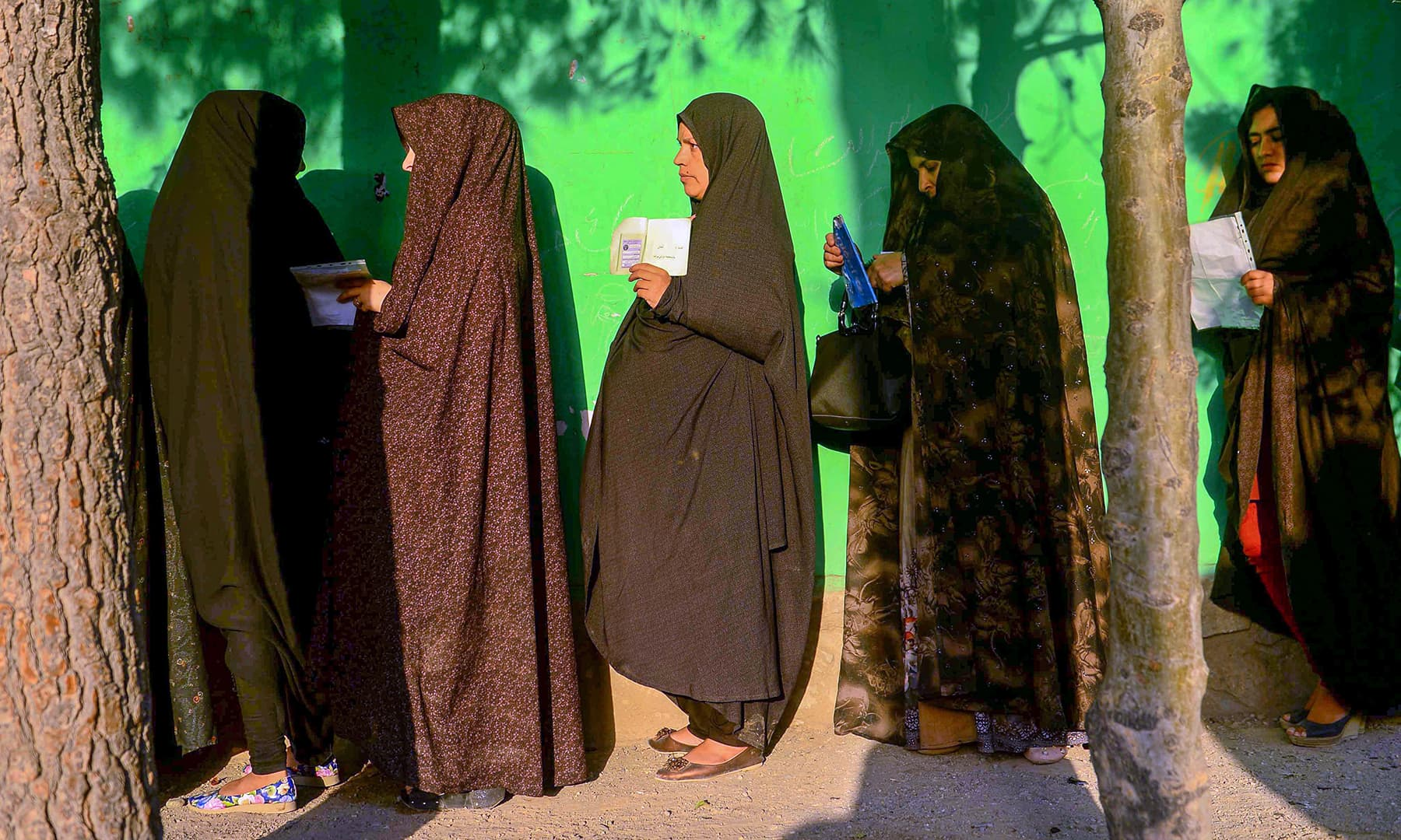 Women queue to cast their vote at a polling station in Herat. — AFP