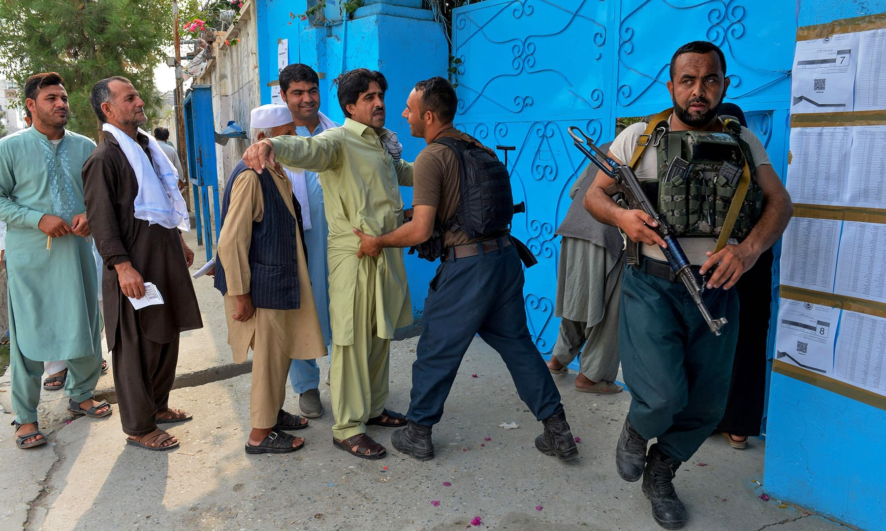 A security force personnel checks a man outside a polling station in Jalalabad. — AFP