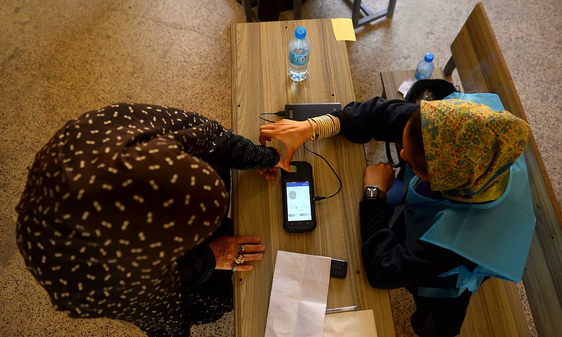 An Independent Election Commission (IEC) official scans a finger of a voter with a biometric device at a polling station in Herat. — AFP